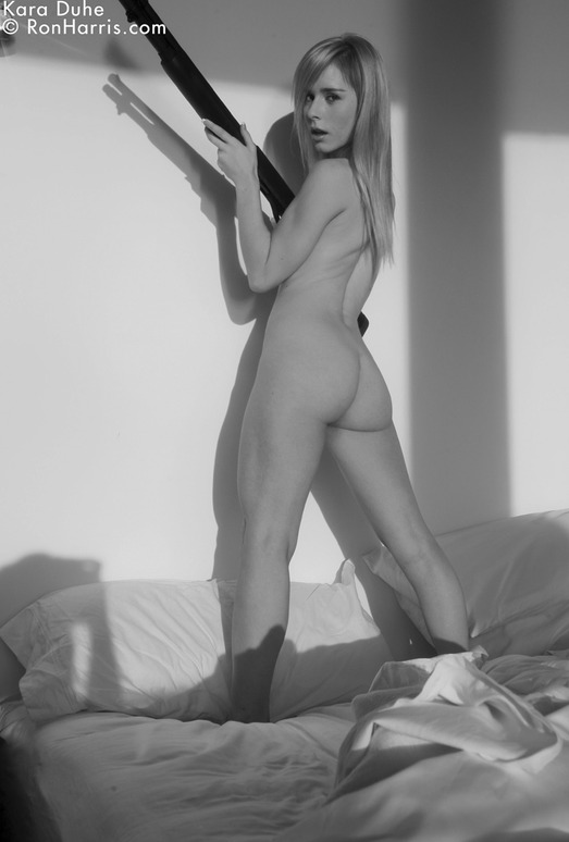 Amazing hot Kara posing nude with a gun on the bed